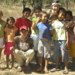 an adult crouching down in the middle of a group of a half-dozen smiling (but distracted) children. They are outside in a dry landscape and have dirt on their feet.