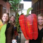 three people pose with large, brightly-painted cardboard cutouts of vegetables.