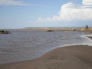 a photo of a pristine beach under a partially-cloudy sky