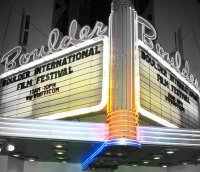 a marquee sign lit up at night featuring the text: boulder international film festival