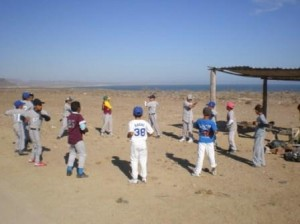 a group of children in mismatching baseball uniforms stand in a circle. They are outside on tightly-packed dirt. A pergola and bright blue, cloudless sky are seen in the background.