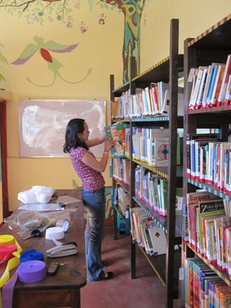 A person with dark shoulder-length hair organizes children's books on a wall-to-wall shelf. Behind them is a brightly-colored mural of a bird and tree.