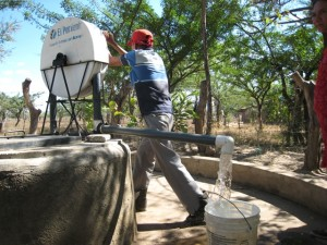 A man in a red hat and blue shirt stands in the center of the frame cranking a handle. We see trees behind him and water coming out of a spigot near his feet.