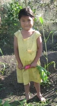 A child with dark hair and skin stands with a radish clutched in both hands. She is wearing a yellow dress and staring at the camera with a bashful expression on her face.