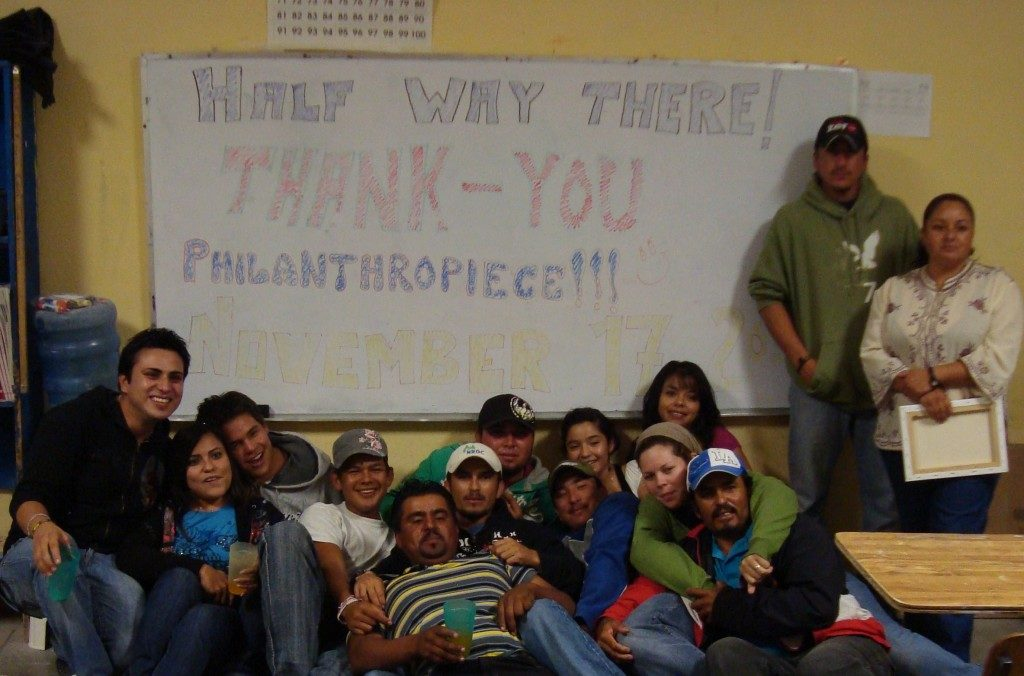 """A group of about a dozen people cluster around a whiteboard that says """"Half Way There! Thank-you Philanthropiece!"""" in red and purple bubble letters."""