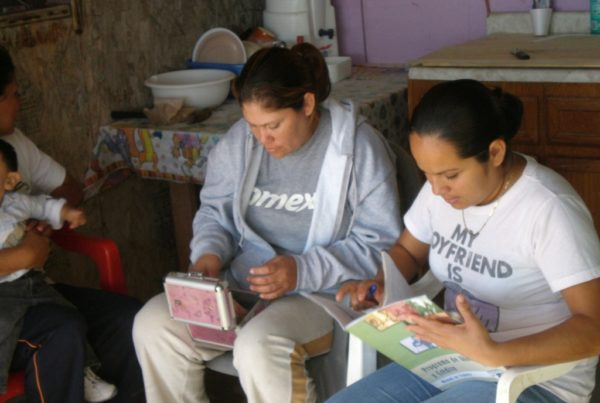 Two people lounge in plastic chairs in casual clothing. The person on the right in focused on a box in their hands; the person on the right is intently leafing through a guide about community banks