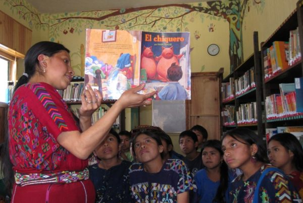 An adult splays the pages of a picture book wide open towards an audience of children. They are all looking at the image intently.