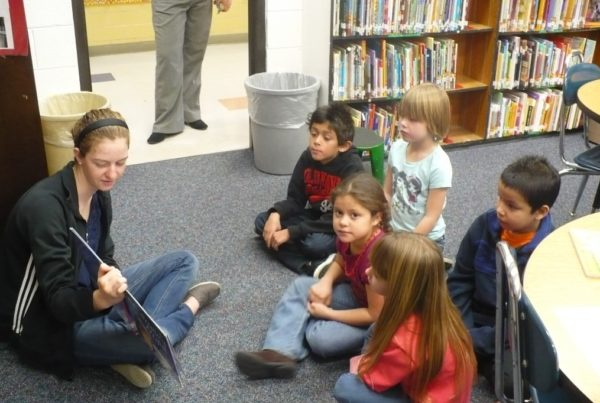 A teenager sitting on the ground reads a book to 5 children, one of whom is looking at the camera.