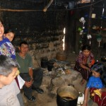 six people gather around pots in a dirt-floored home.