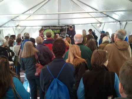 Dozens of people stand huddled under a white event tent, looking at a stage