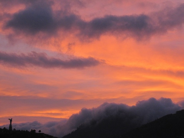 A cloudy sunset is shown. The hues range from dark plum purple to bright coral.