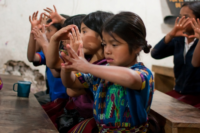 two rows of guatemalan children in brightly-colored tunics touch their fingertips together as part of a group song. the photo is taken in perspective, and the child closest to us looks like she is concentrating VERY hard