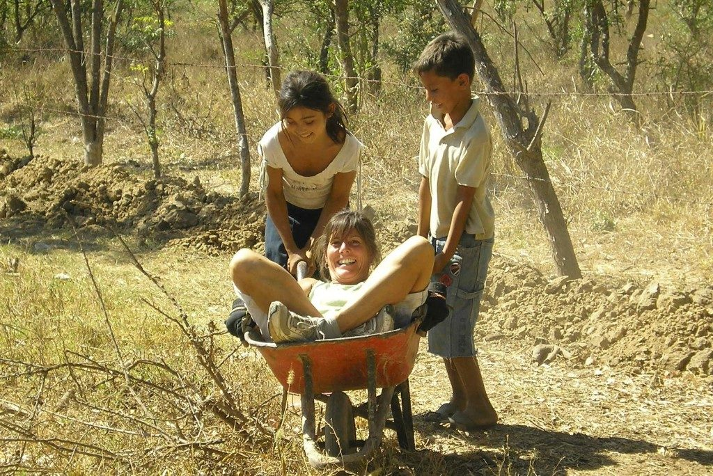 Joanie, wearing shorts and sneakers, lies stomach-up and legs-crossed in an orange wheelbarrow. The wheelbarrow is being lifted by two children, one of whom is smiling and one of whom is visibly straining