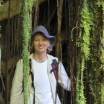 Julie stands behind a fist-thick vine covered in moss. She is wearing a white shirt, a light tan rain jacket, and a floppy fisherman hat
