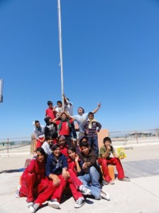 About 20 people, most of them wearing red, cluster around a flag pole for a group picture. some are mid-laugh, some are making funny faces, and one has their arms raised above their head in exuberance