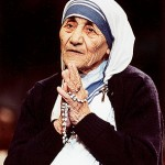 Mother Teresa in a square-close cropped portrait. She wears great swaths of black and white fabric around her head and arms, and her hands are clutched around prayer beads