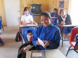 Five teenagers are seen in two rows of school desks. The one closest to us is grinning and holding a sheet of white paper