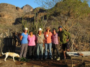Six people stand in hiking clothes in front of a desert mountain. A large white dog sniffs at their feet in the bottom left corner