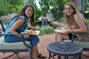 two women sit on cushioned chairs in an outdoor patio area. they are holding plates of food and smiling at the camera