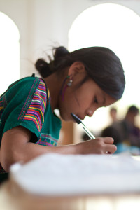 a child with dark hair and a bright emerald tunic hunches over schoolwork, writing
