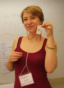 "A person in a red tank top stand smiling in front of a whiteboard. They are wearing a lanyard nametag and holding up a slip of paper with the letter ""e"" on it"