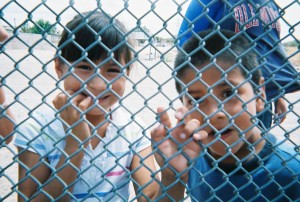 Two children grasp the links of a wire fence. the photo is taken from the other side