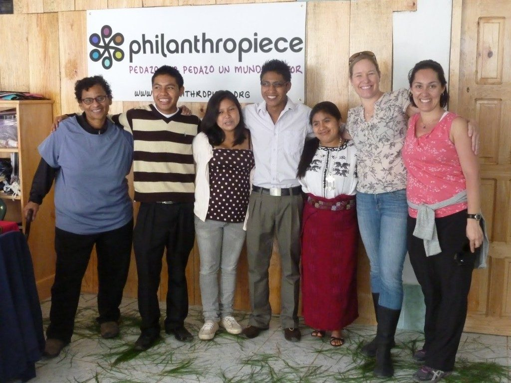 seven people stand in front of a philanthropiece poster nailed to a wood-paneled wall. They have their arms around each other, looking in different directions and smiling