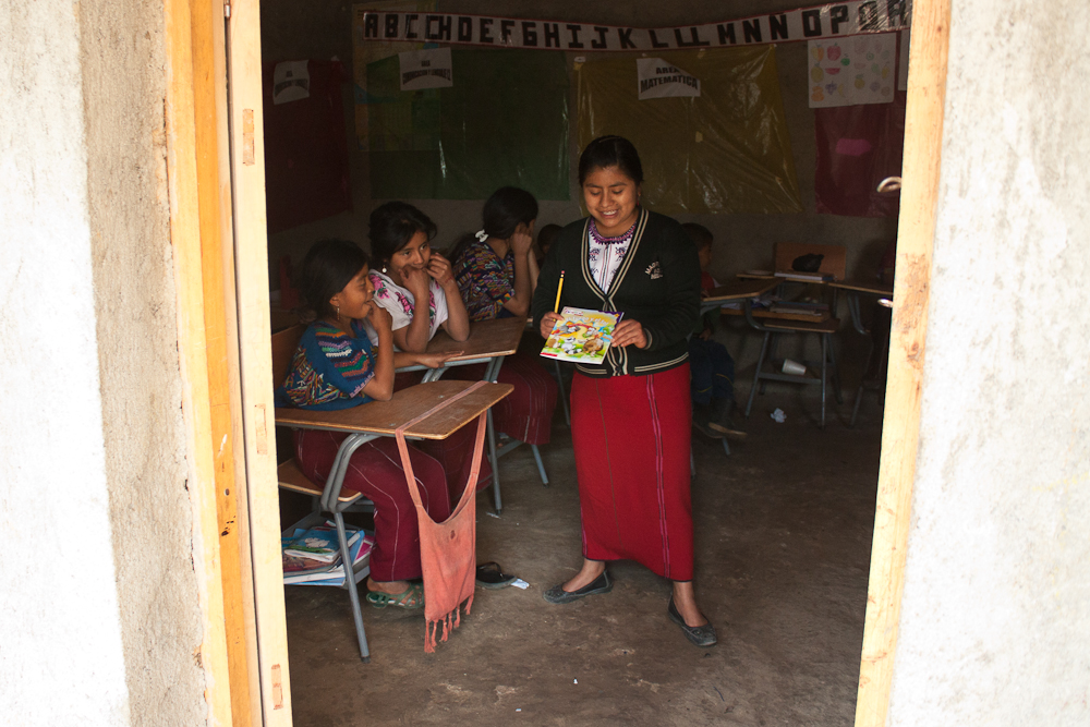a photo taken through an entryway reveals three children at school desks and one standing up with a book in their hands
