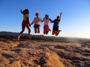 four teenagers are pictured mid-jump against a bright blue sky and desert ground