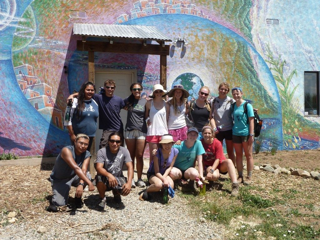 14 people stand in bright sun in front of a vibrant mural depicting the earth, greenery, and abstract waves. They are wearing summer clothes and sunglasses.