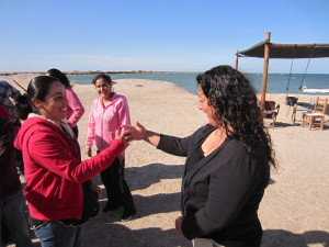 Two women stand on a beach, facing each other, their right arms extended. Their ring fingers are touching. In the background, we see the water, a pergola, and two people in pink sweatshirts.