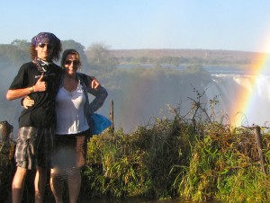 Two people stand on the left side of the frame with their arms wrapped around each other. They are wearing sunglasses and shorts, and we see a rainbow, a waterfall, and blue sky in the background.