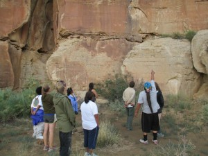 Eight people stand facing a huge, sheer cliff. The photo is taken from behind.