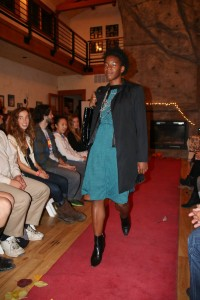 A black woman with short curly hair is pictured mid-stride down a red carpet. She is wearing a blue knee-length dress, an oversized gray blazer, and black heeled boots. In the background, we see a singular row of audience members lining the runway and a rock wall.