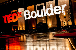 "Huge 3D letters spelling ""TEDx Boulder"" hang in front of a window and reflect on the wet pavement."