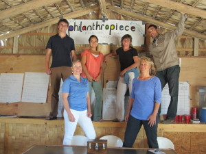 "Six people post symmetrically around a hand-drawn poster that says ""philanthropiece."" In the background, we see a pitched ceiling made of unfinished wood, presumably newly-constructed."