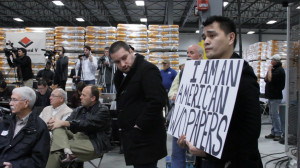 "A group of people gather in an industrial warehouse with shipping pallets in the background. The one closest to us is holding a sign that says ""I am an American w/o papers."""