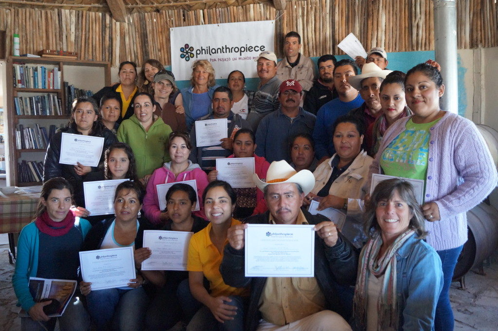 Three dozen people gather in front of a Philanthropiece sign. Many are holding official-looking certificates. In the background, we see a book shelf and a branch-thatched wall
