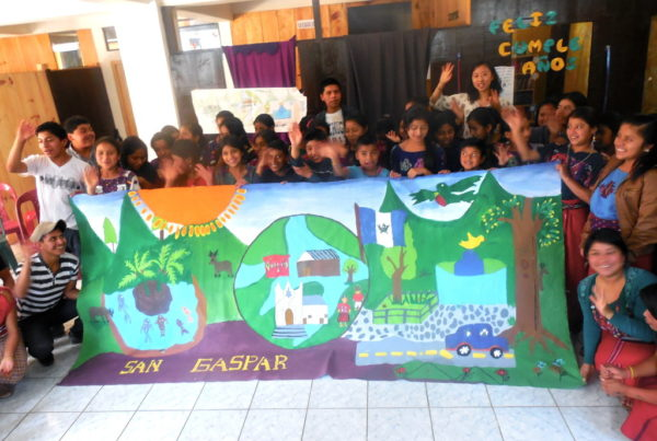 """Dozens of children stand around a hand-painted banner that says """"SAN GASPAR."""" They are in motion, waving and blurry."""