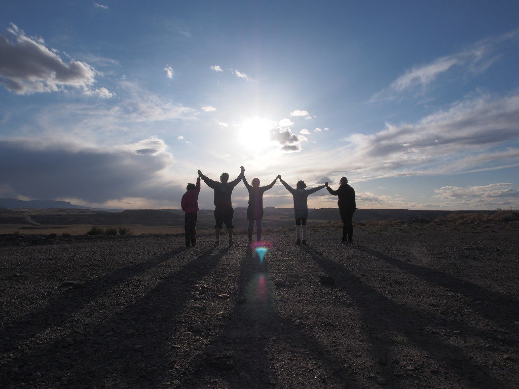 Five people stand in front of a bright sky. They are silhouettes: hands joined, arms raised in apparent victory.