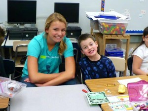 Rachel poses with a young child at a classroom table. They are leaning in towards each other, almost touching, with full-toothed smiles.