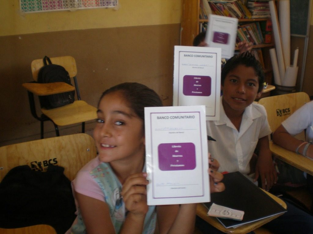 "Three children sit in classroom desks and hold up pamphlets entitled ""Banco Comunitario."" They are smiling, and the one farthest from us is in mid-motion and blurry."