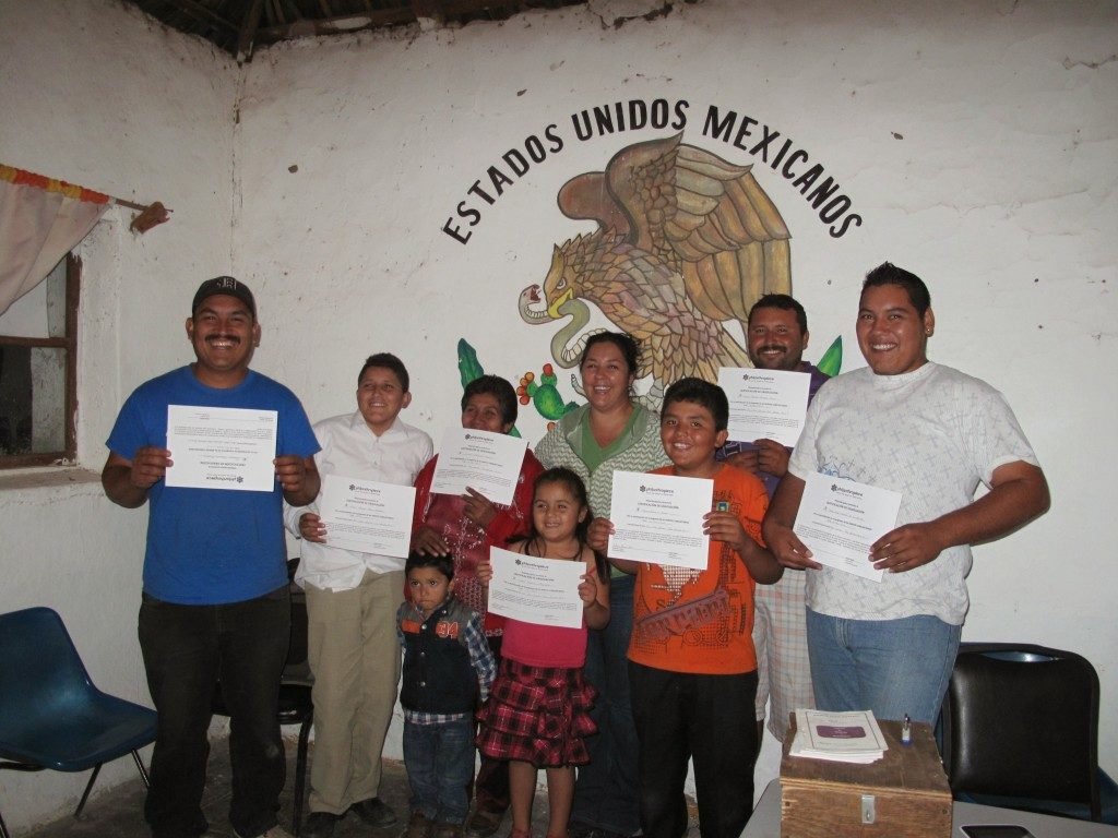 "Seven adults and two children pose in front of a wall that says ""Estados Unidos Mexicanos."" They are smiling and holding up white paper certificates."
