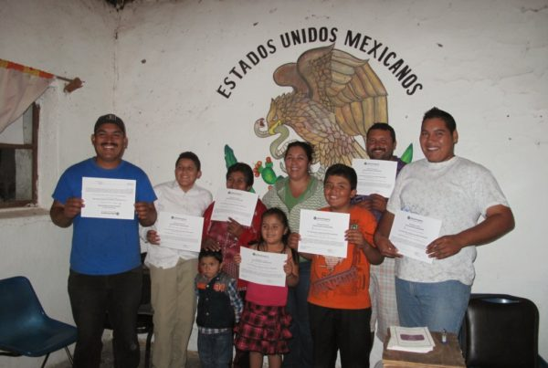 """Seven adults and two children pose in front of a wall that says """"Estados Unidos Mexicanos."""" They are smiling and holding up white paper certificates."""