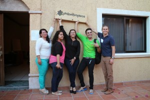 "Five people pose in front of a beige stucco wall and hold a wooden sign that says ""Philanthropiece."""