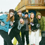 Six people dress in snow gear strike silly poses in front of a wooden lodge.