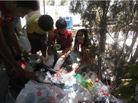 Four people stand in the shade of a couple sparse trees, bent over a large pile of plastic bottles