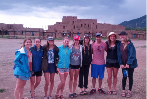 Nine people stand in a line with their arms around one another. In the background, we see a traditional pueblo structure and dark clouds.