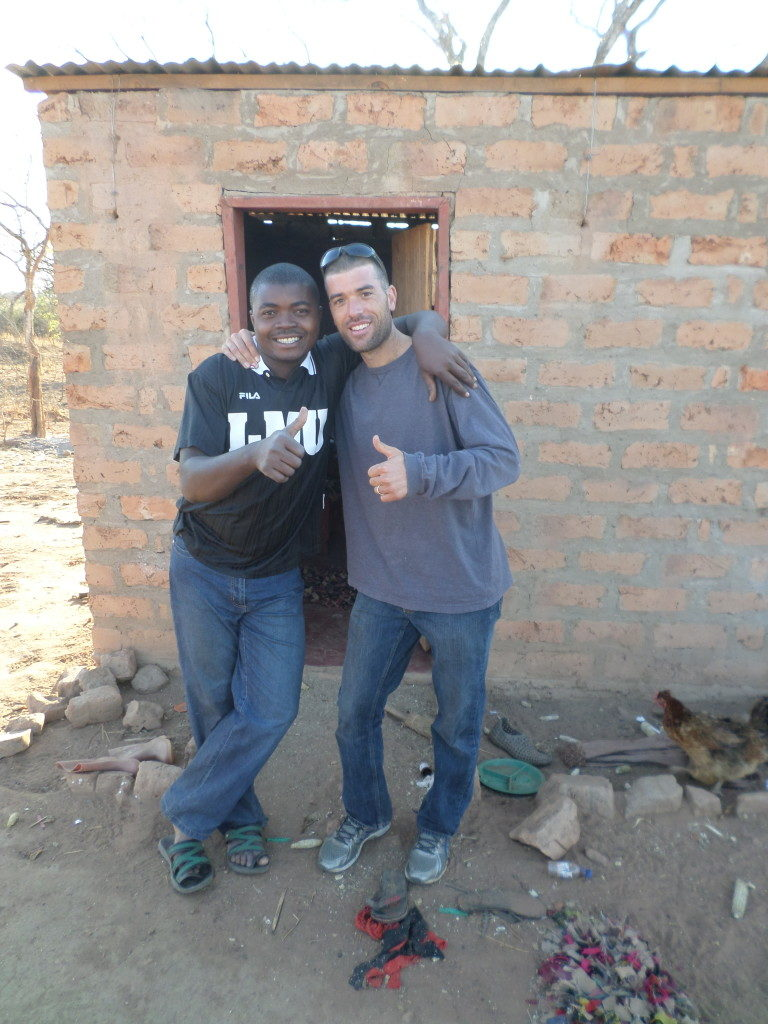 Two men stand in front of a squat brick shelter with their thumbs up and arms around each other. On the right side of the frame is a chicken pecking its way towards their feet.