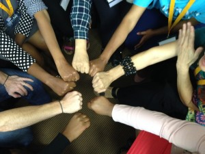 A photo is taken from above of people putting their fists into the middle of a circle. Many skin tones, bracelets, and types of shirts are seen.